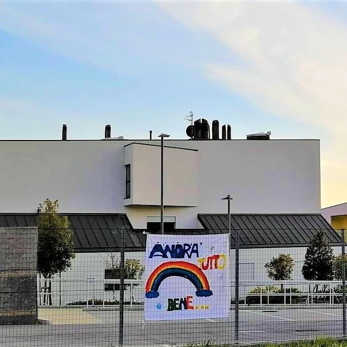 """Gli edifici del nuovo Centro Nazionale, con uno striscione dove c'è la scritta in lettere colorate """"Andrà tutto bene"""" e un arcobaleno."""