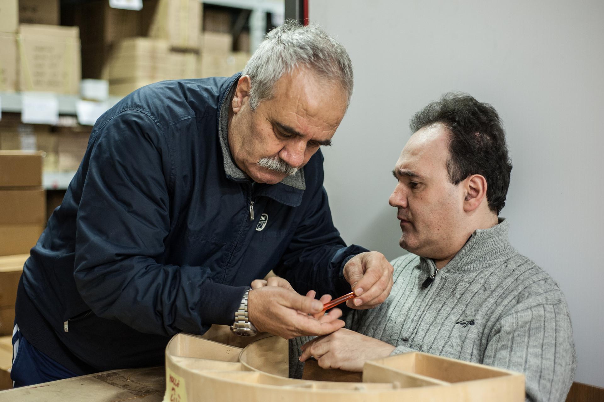 Alberto, un utente adulto, e suo padre Gianfranco, lavorano insieme un oggetto fatto di legno.