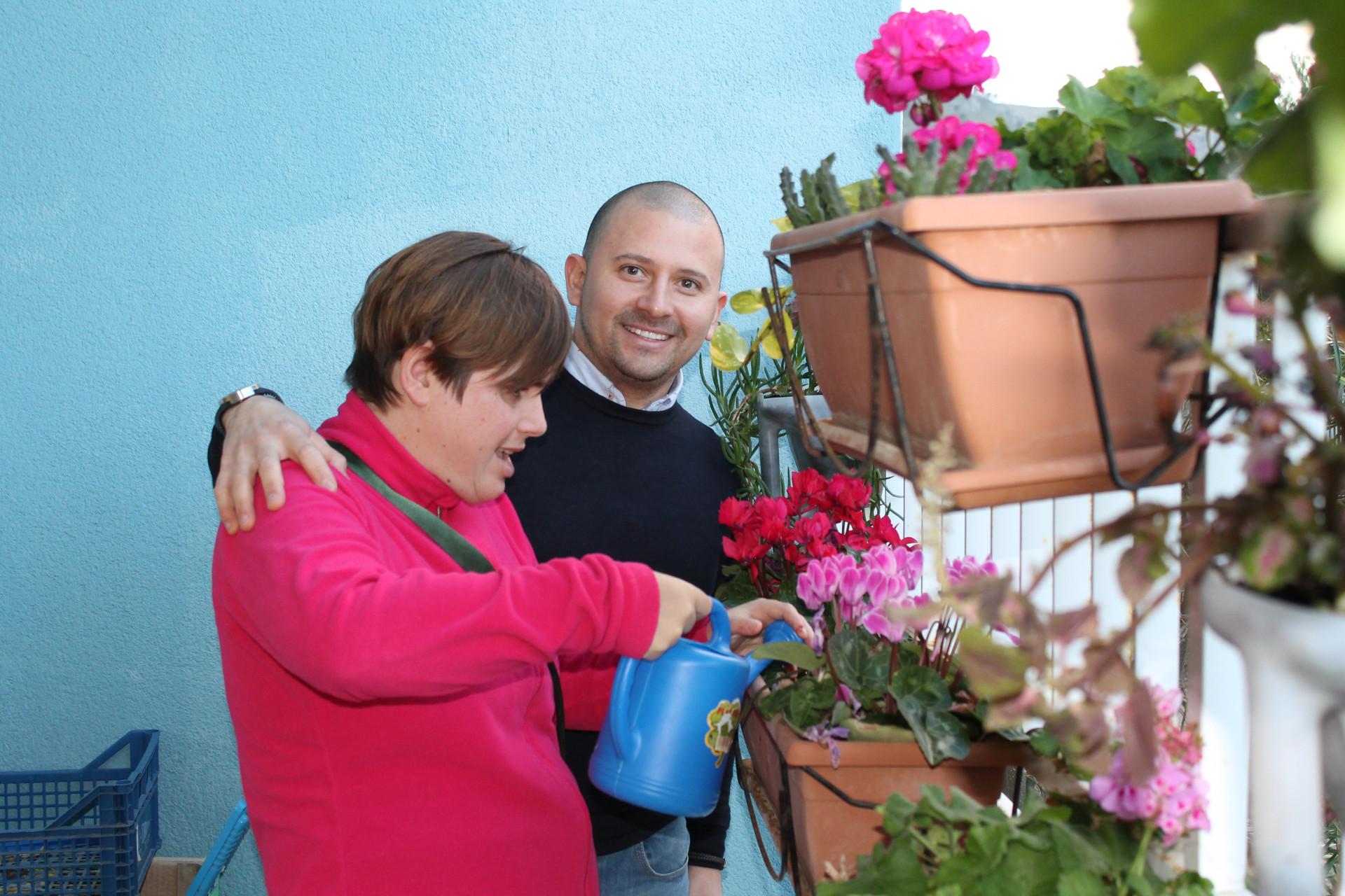 Gerri sorride mentre aiuta una persona con sordocecità ad innaggiare un vaso di fiori.