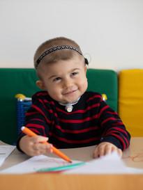 Bimbo con sindrome di Charge sorride mentre disegna con un pennarello arancione