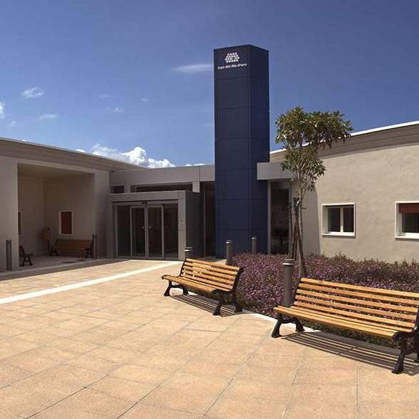 Grandangolo del Centro di Termini Imerese. L'ingresso piastrellato è centrale, due panchine e un piccolo giardino con dei fiori e due alberelli sono sulla destra, mentre l'edificio è grigio. Il cielo è azzurro.
