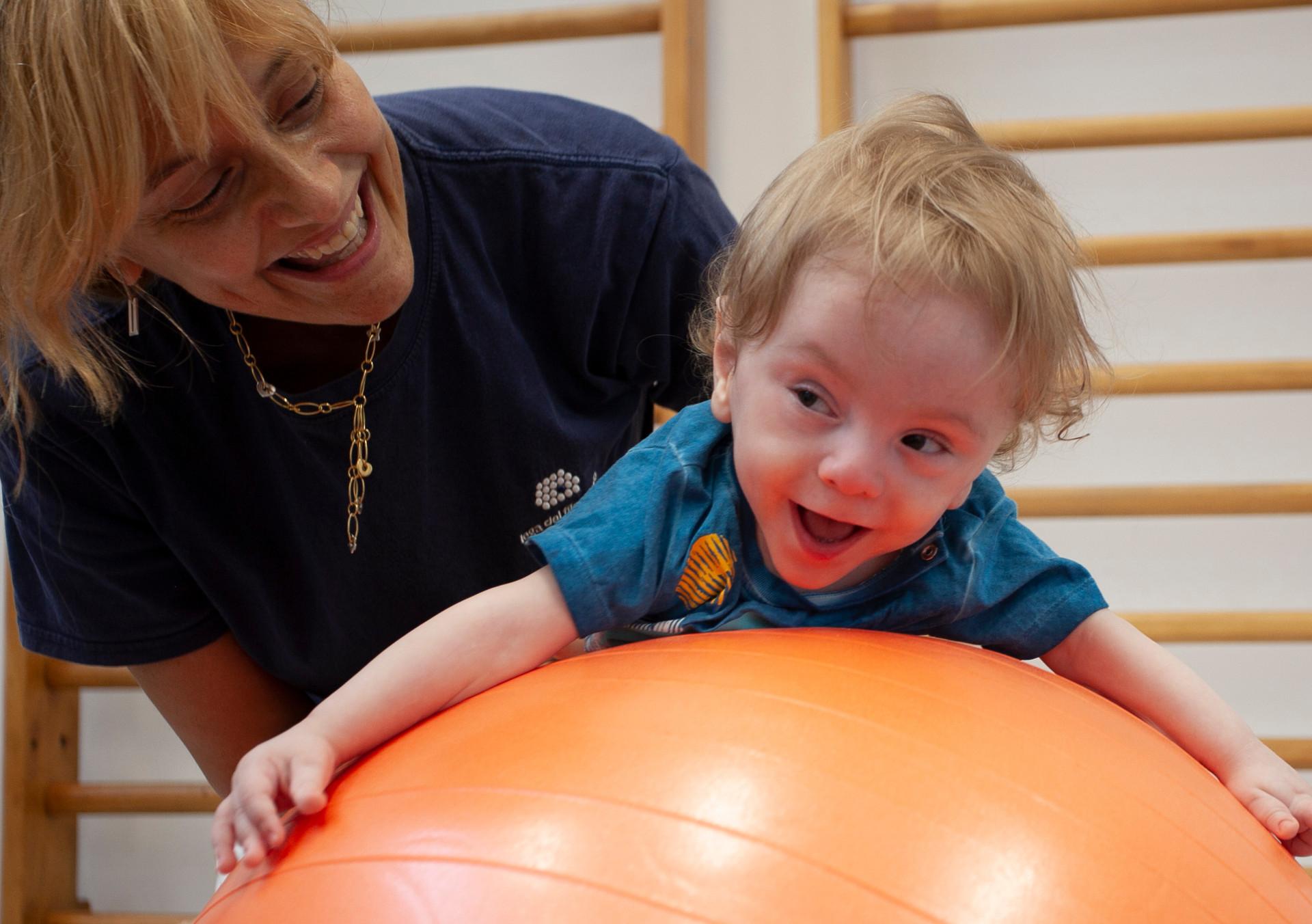 Gabriele, un bambino seguito dalla Lega del Filo d'Oro fa attività di fisioterapia con la sua fisioterapista, che lo sorregge in equilibrio sdraiato su una grande palla arancione. Entrambi ridono divertiti.