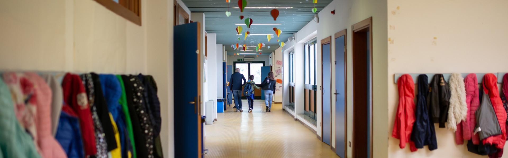 Francesco entra a scuola tenuto per mano da mamma e papà. Sono inquadrati di spalle mentre camminano lungo i corridoi