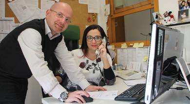 Andrea e Eleonora, due centralinisti della Lega del Filo d'Oro, sono fotografati mentre lavorano. Eleonora ha la cornetta del telefono appoggiata all'orecchio ed è seduta alla scrivania. Andrea sta lavorando al computer. Entrambi guardano verso la fotocamera.