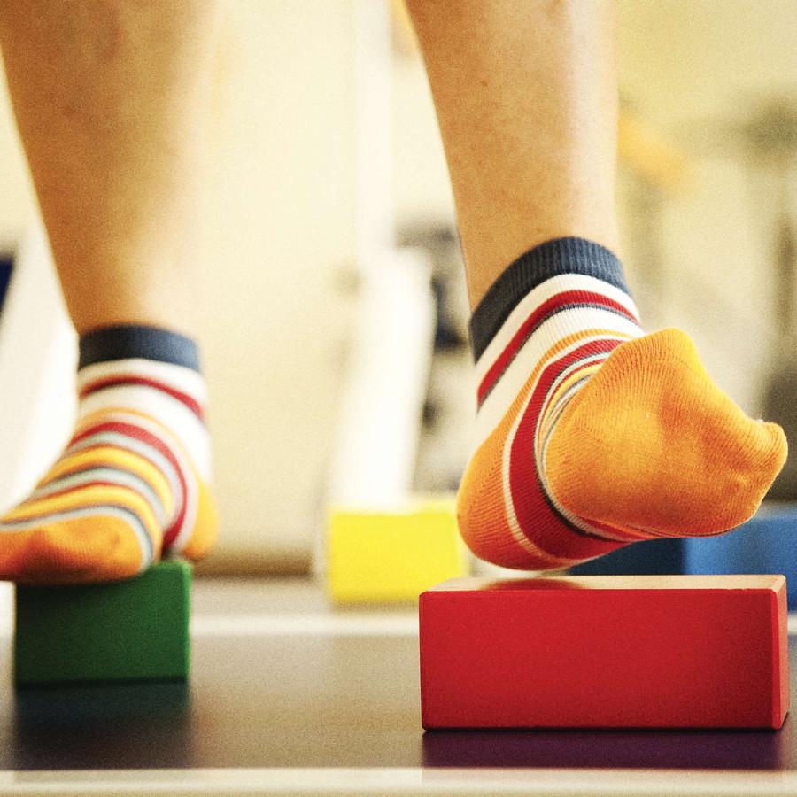I piedi di un utente durante un attività che prevede di camminare appoggiando i piedi solo su dei cubetti colorati.