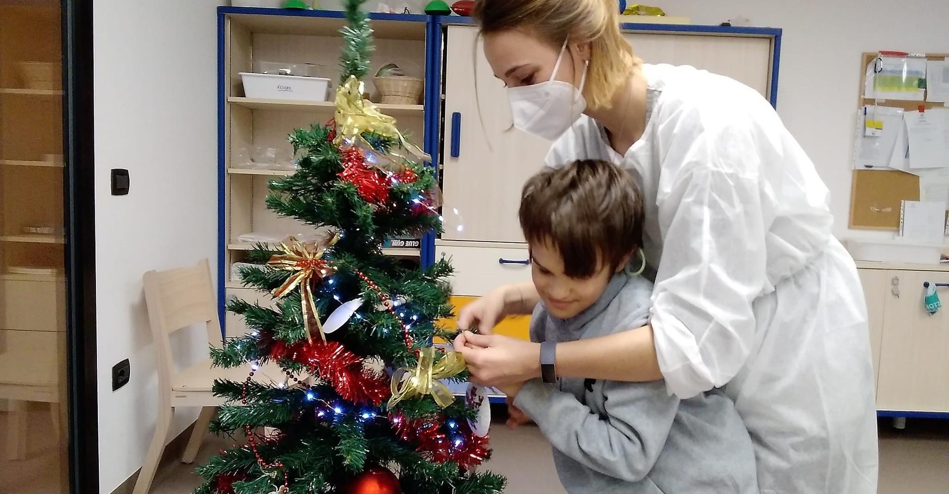 Un'operatrice e un bambino ospite del Centro Nazionale decorano un albero di Natale con palline e addobbi.