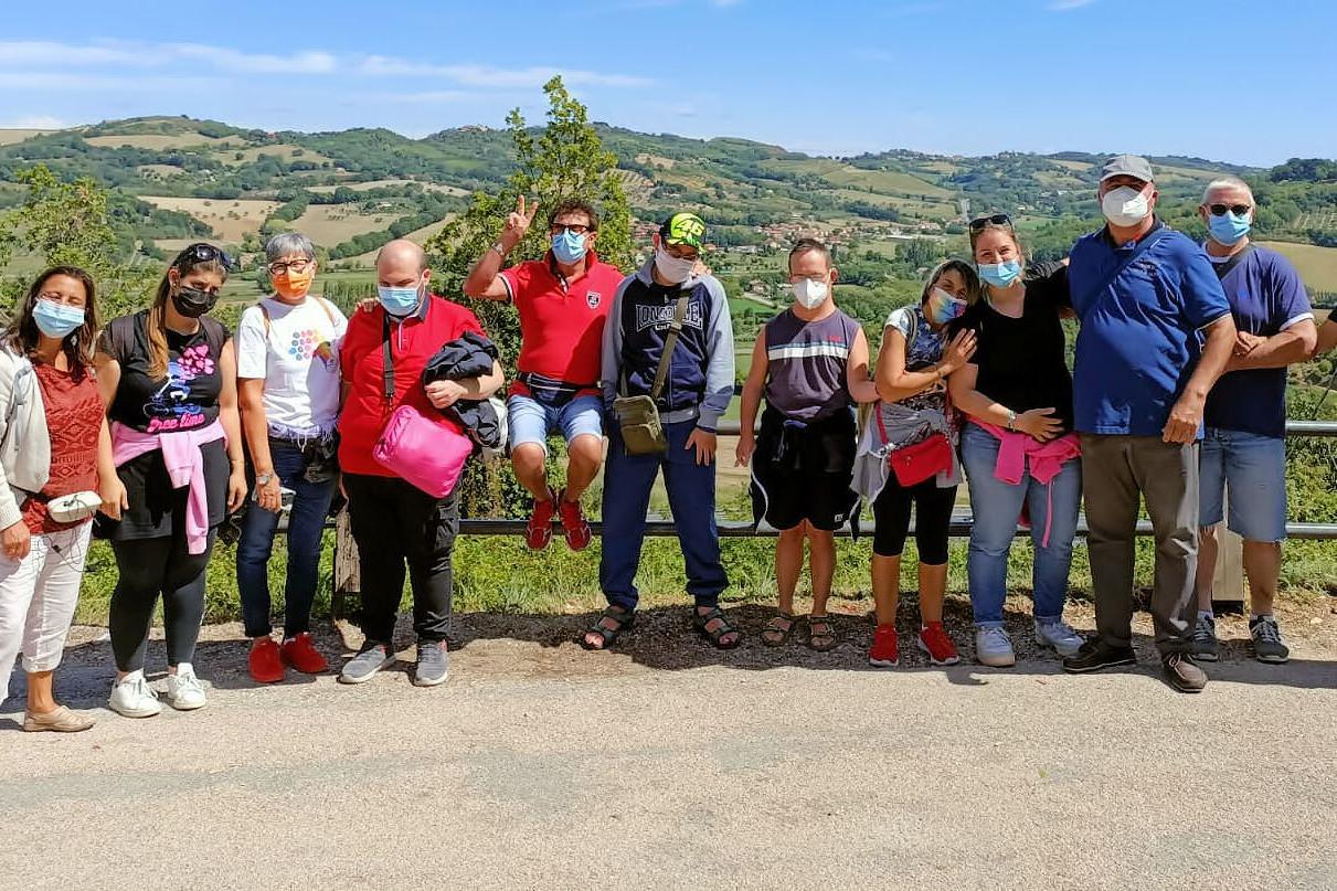 12 persone tra utenti, operatori e volontari posano in piedi per una foto di gruppo. Dietro di loro ci sono le colline.