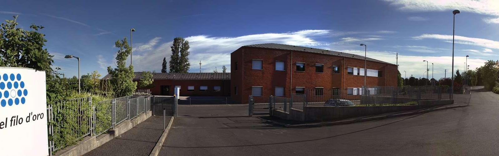 Foto a campo largo della Sede di Lesmo. A sinistra il cartello con il logo della Lega del Filo d'Oro e un cancello, mentre centralmente si vede l'edificio principale in mattoni rossi. La strada continua a si allontana sulla destra. Il sole splende nel cielo azzurro, con qualche nuvola.