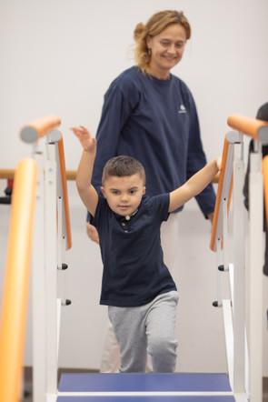 Leonardo, un bambino affetto della sindrome di Charge, sta svolgendo attivitò di fisioterapia con Francesca, fisioterapista del Centro di Osimo della Lega del Filo d'Oro. Leonardo sta salendo delle scale