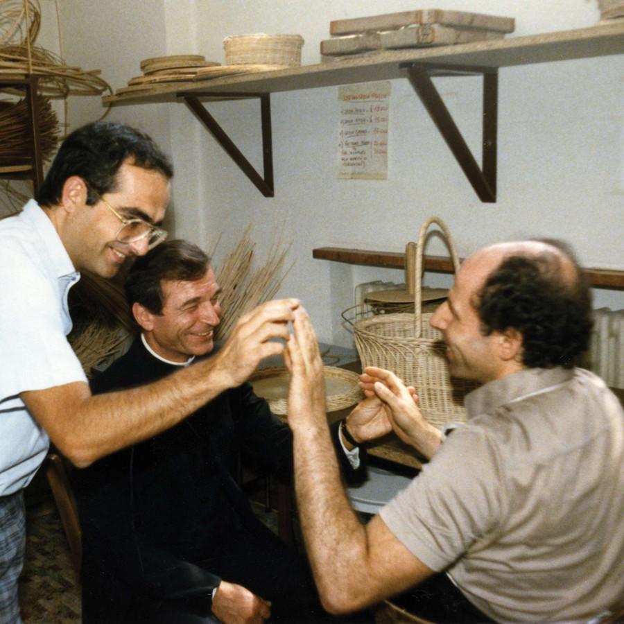 Un utente sordocieco incontra il Monsignor Francesco Casalini e un altro uomo, che qui saluta con tocco di mano. Tutti e tre sono sorridenti.