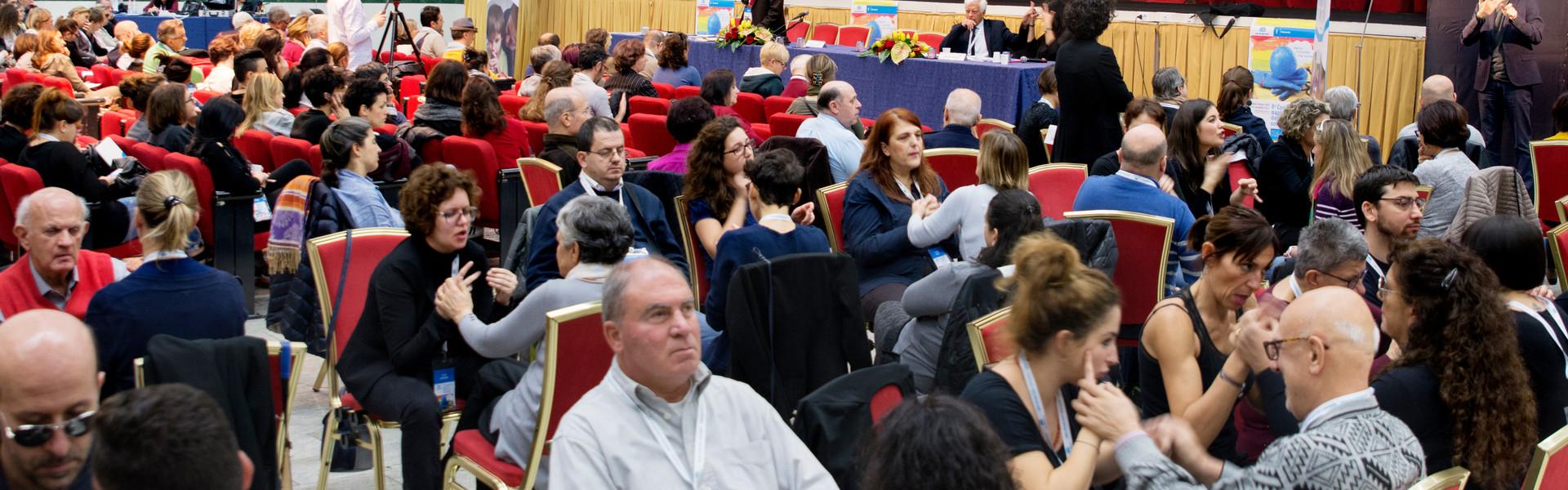 Conferenza nazionale delle persone sordocieche anno 2018. vista della platea. tante persone sordocieche e interpreti comunicano tra loro in LIS tattile e Malossi