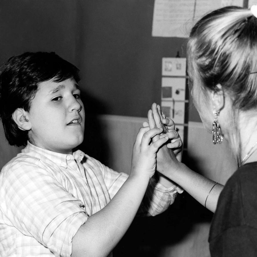 Un bambino sordocieco comunica tramite il tocco della mano con una donna. Immagine degli anni '80 in bianco e nero.