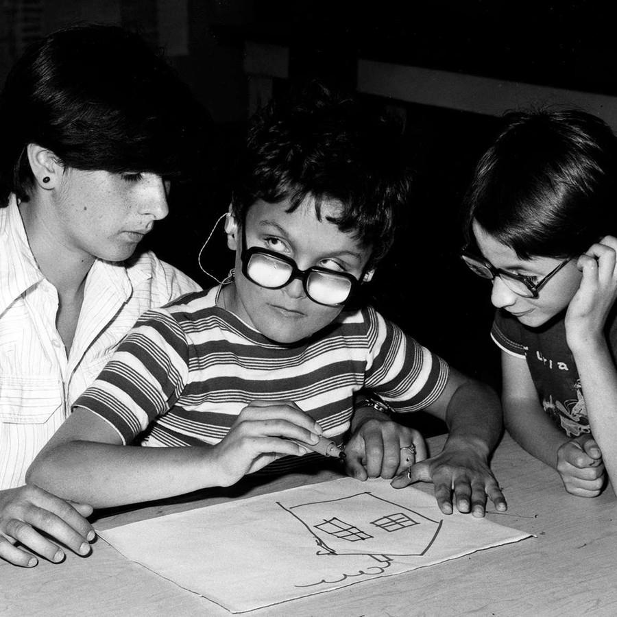 Foto scattata negli anni '70 e quindi in bianco e nero. Un bambino ospite dell'Istituto di Riabilitazione di Osimo sta disegnando una casa con un pennarello, seduto sulle gambe di un'operatrice. Un altro bambino guarda incuriosito.