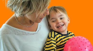 Edoardo, un bambino ospite della Lega del Filo d'Oro, sorride mentre gioca con una palla fucsia e viene preso in braccio da un'operatrice. Lo sfondo dell'immagine è arancione.