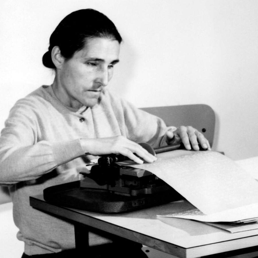 Sabina Santilli, fondatrice della Lega del Filo d'Oro, alla sua scrivania impegnata alla scrittura in dattilobraille. L'immagine è in bianco e nero.