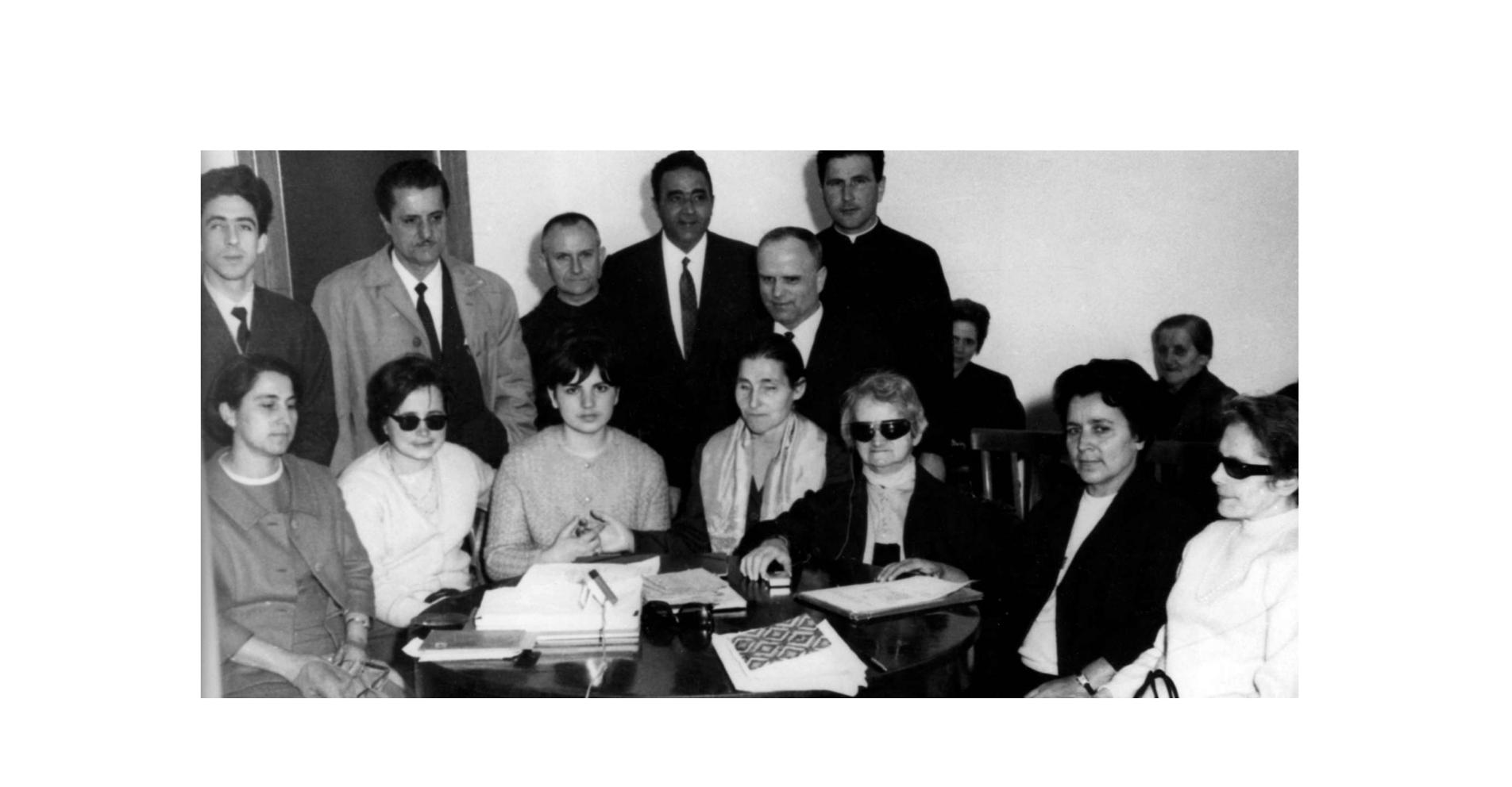 Foto di gruppo dei fondatori della Lega del Filo d'Oro. Sette donne tra cui anche Sabina Santilli, sono sedute attorno ad un tavolo. Dietro di loro sei uomini. L'immagine è in bianco e nero.