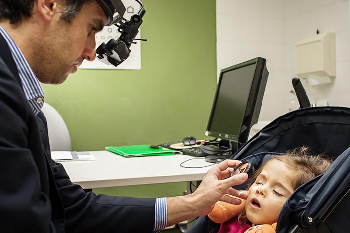 Il Dr.Pantanetti visita una piccola utente nell'ambulatorio oculistico di Osimo. La bambina è seduta nel passeggino, mentre l'oculistale osserva l'occhio destro con una lente d'ingrandimento.