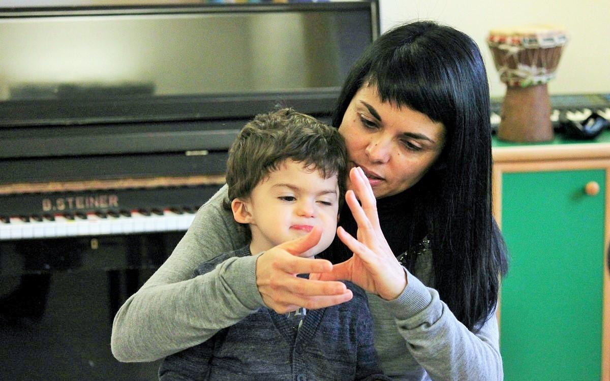"""Mamma Simona tiene in braccio Agostino e gli """"canta"""" una filastrocca aiutandosi con la LIS"""