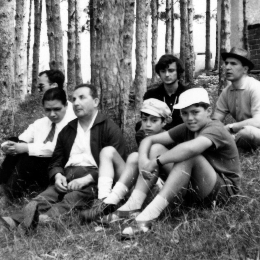 Un gruppo di uomini, alcuni molto giovani, tra cui alcuni utenti della Lega del FIlo d'Oro, si riposano seduti sull'erba in mezzo a un boschetto.