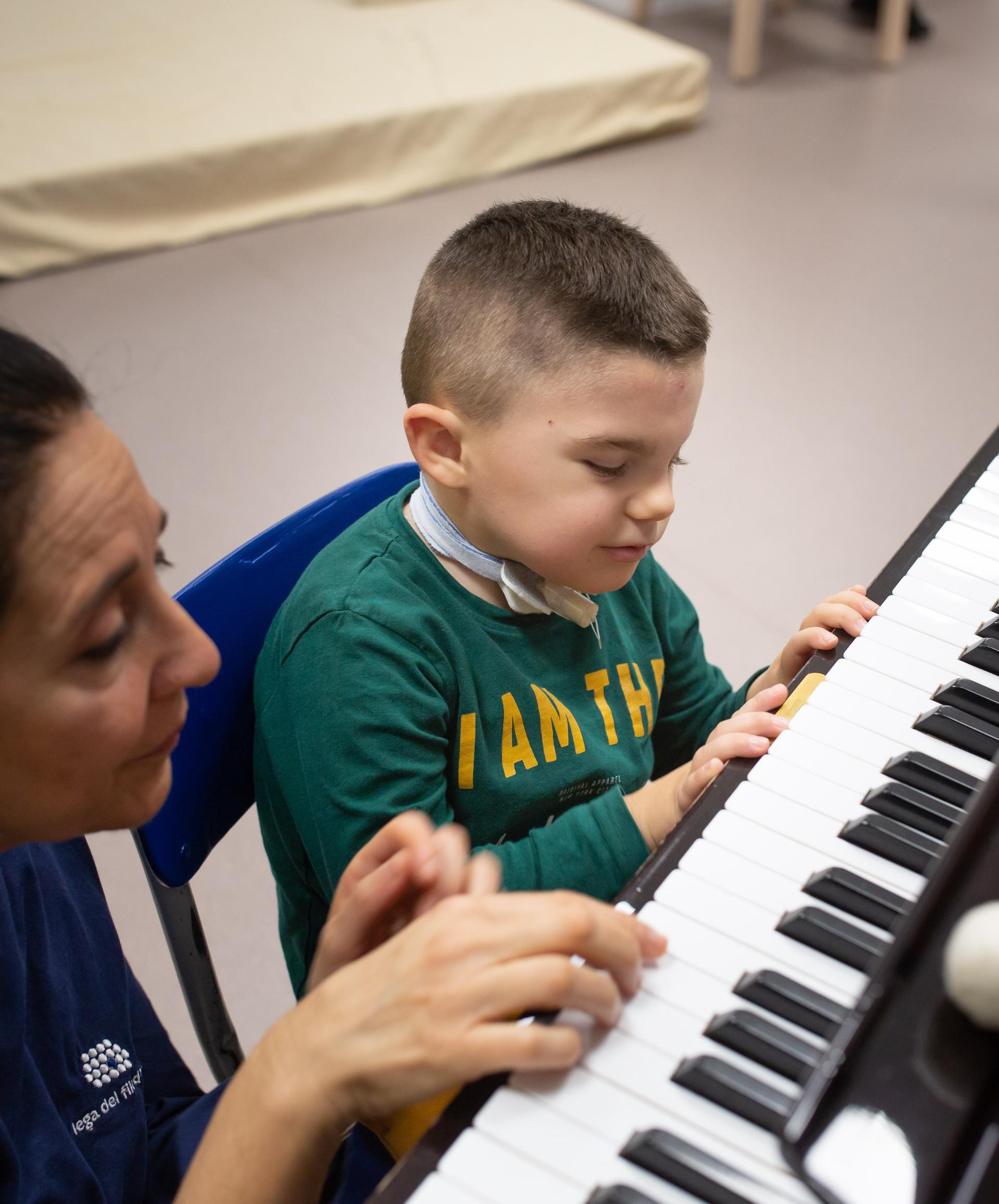 Leonardo, un bambino affetto della sindrome di Charge, suona al pianoforte con Fimmetta, musicoterapista del Centro di Osimo della Lega del Filo d'Oro