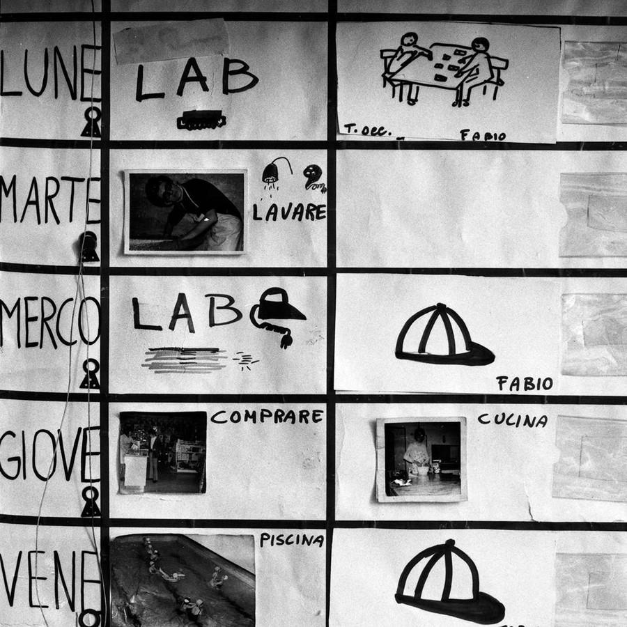 In bianco e nero, la foto ritrae un calendario pittografico, con una tabella in cui sono segnati i giorni della settimana, le attività e gli incaricati di queste.