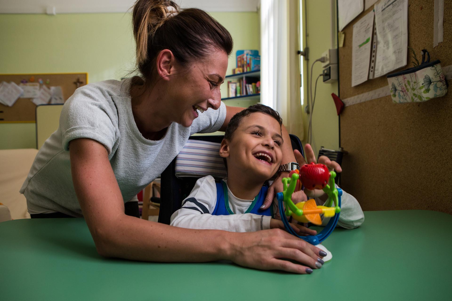 Francesco, un bambino ospite della Lega del Filo d'Oro, gioca con un giocattolo. Un'operatrice lo abbraccia e ride insieme a lui.