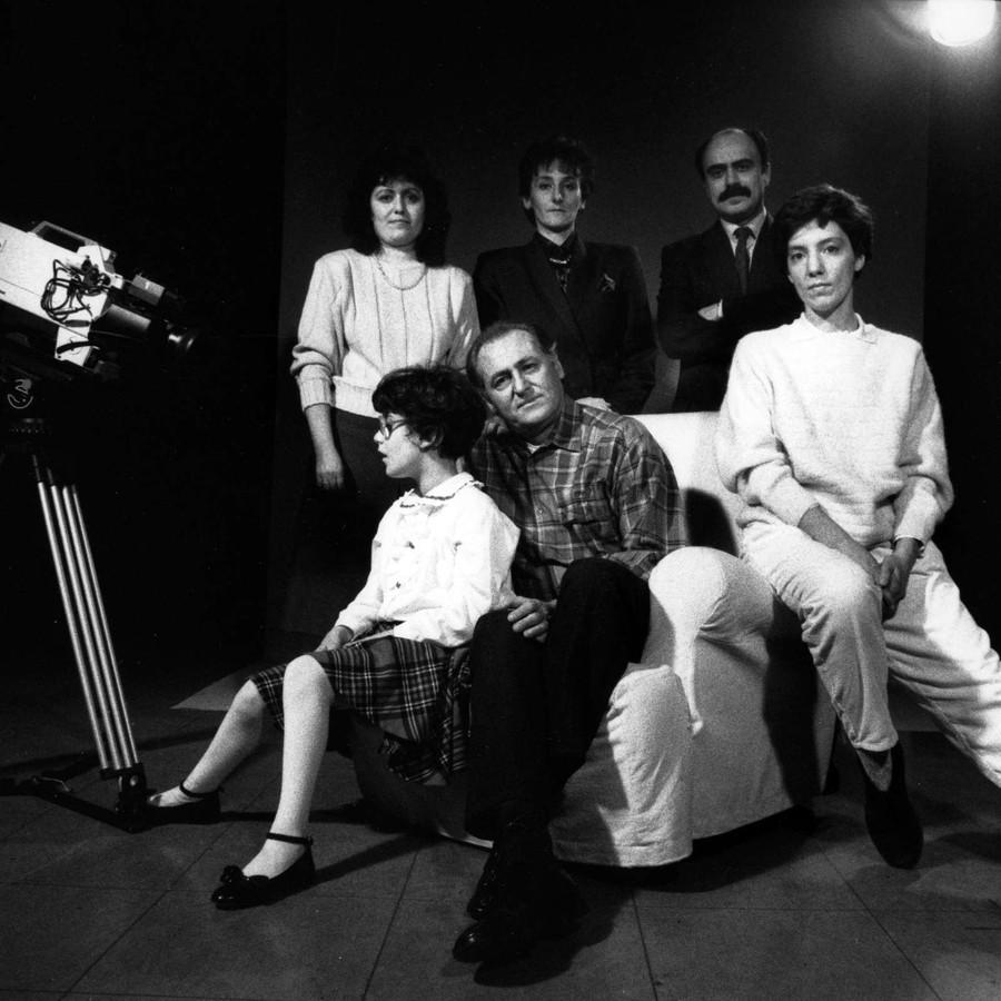 Foto in bianco e nero, scattata sul set di una campagna promozionale nel 1989. Si vede la macchina da presa e un gruppo di persone: tre sono sedute su una poltrona e sono una donna, Renzo Arbore e una bambina sordocieca; altre tre sono in piedi dietro di loro, si tratta di due donne e Rossano Bartoli.