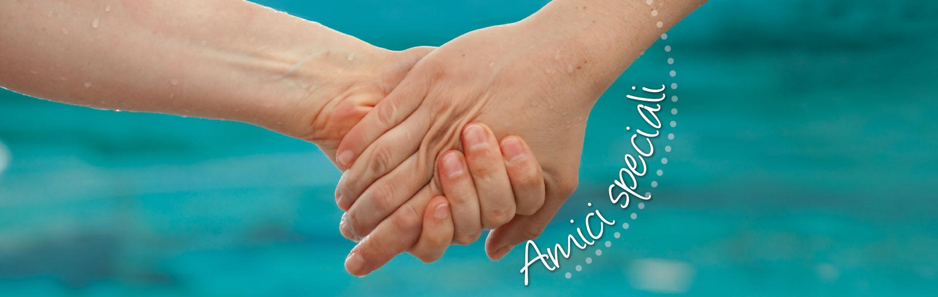 """Due mani si stringono, dietro si vede sfuocata l'acqua di una piscina. Vicino alle mani c'è la scritta """"Amici Speciali""""."""