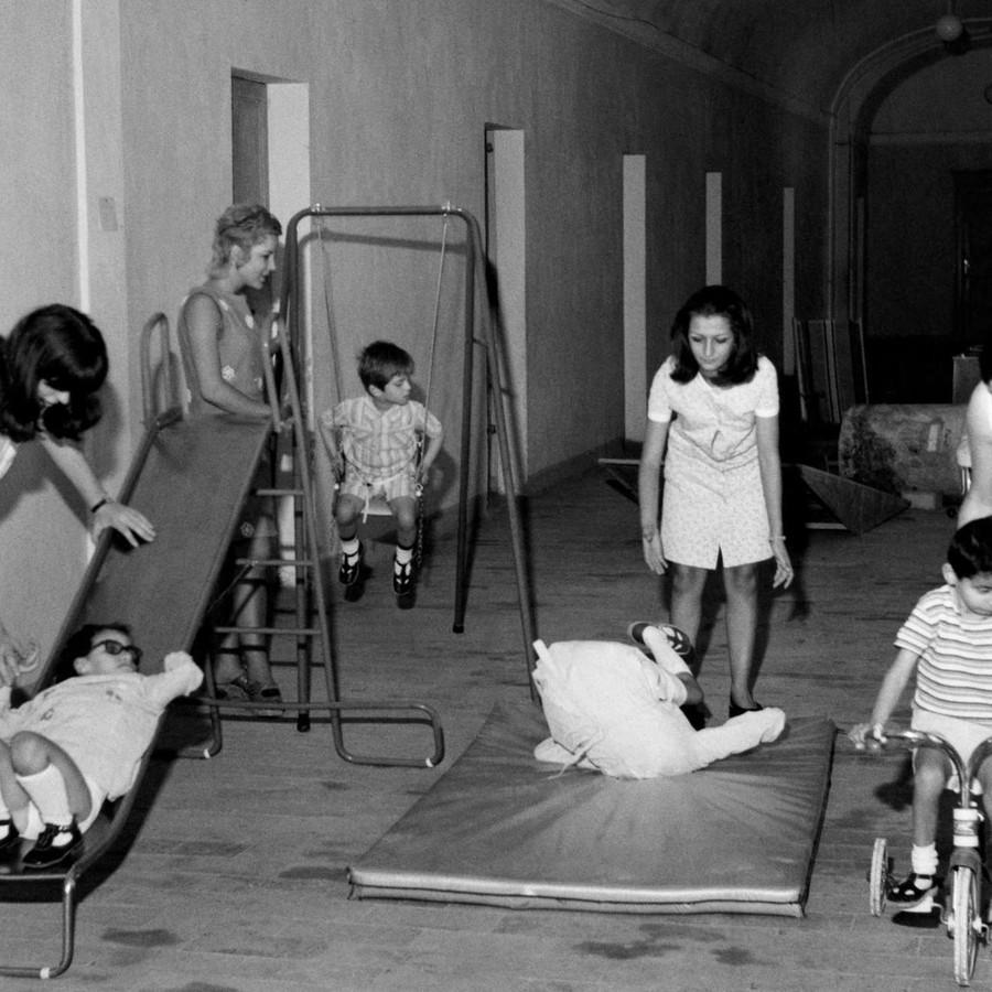 Foto in bianco e nero del 1970, che ritrae giovani utenti sordociechi impegnati in attività di gioco con l'aiuto di operatrici. In un'ampia sala con tante porte, sono stati disposti uno scivolo, un'altalena, un materassino e una bicicletta. Ogni strumento è usato da un bambino, ogni bambino è seguito da un'operatrice.