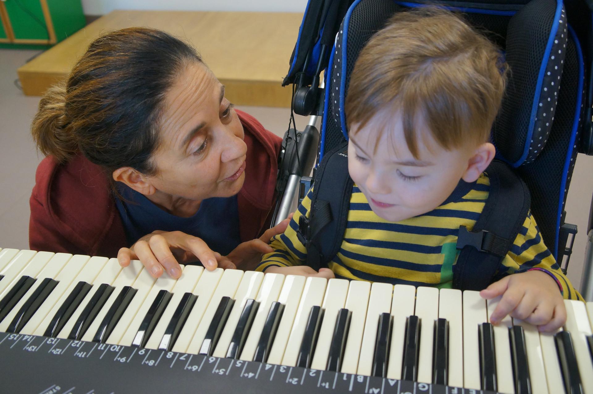 Fiammetta Musicoterapista del Centro di Osimo, insegna al piccolo Edoardo a suonare i tasti di un pianoforte