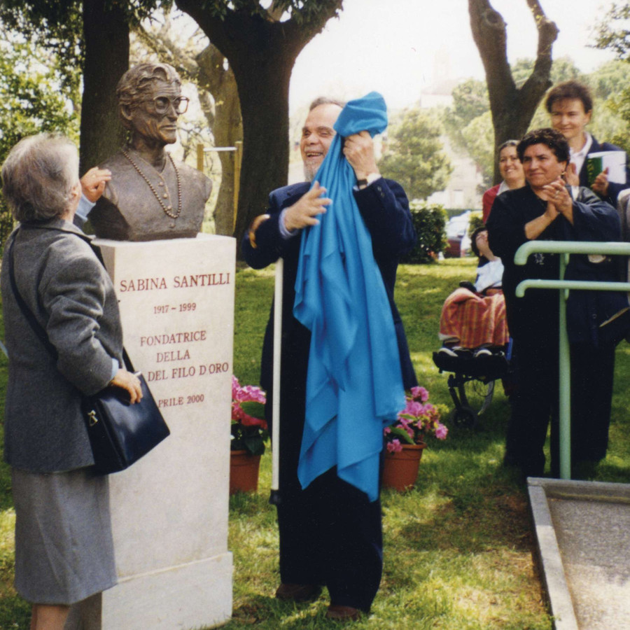 Due persone hanno appena tolto un velo azzurro dal busto dedicato a Sabina Santilli. Presente una piccola folla che applaude.