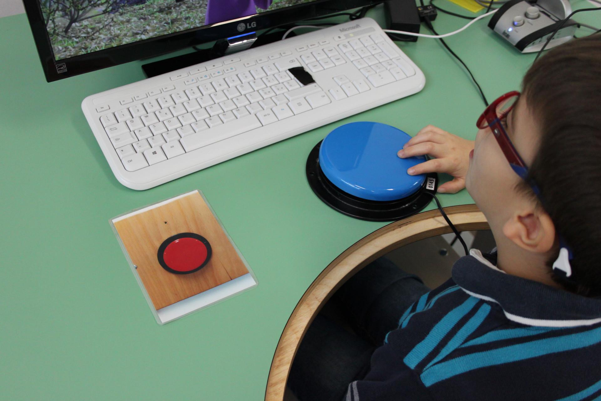 Un bambino, utente della Lega del Filo d'Oro, guarda uno schermo e preme un pulsante blu appoggiato davanti a lui per dare comandi al computer.