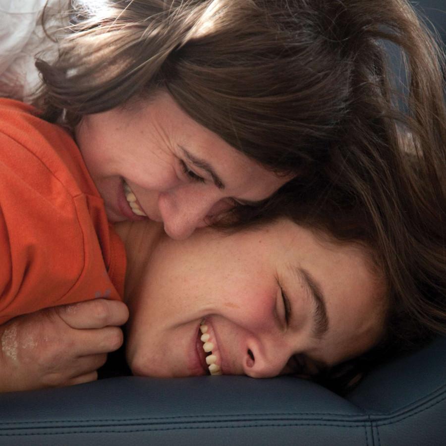Primo piano dei volti di un bambino ospite della Lega del Filo d'Oro e di una donna. Il ragazzo è appoggiato con la testa su un materasso e la donna è appoggiata su di lui e lo abbraccia. Entrambi sorridono.