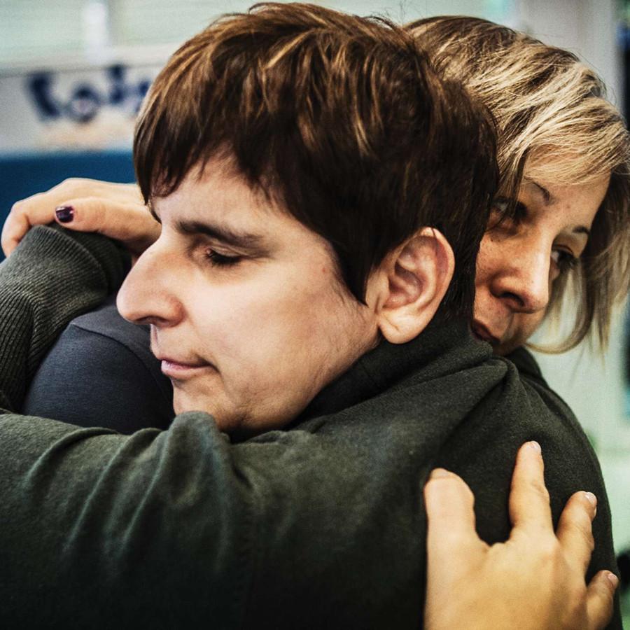 Una donna e un'utente della Lega del Filo d'Oro si abbracciano.