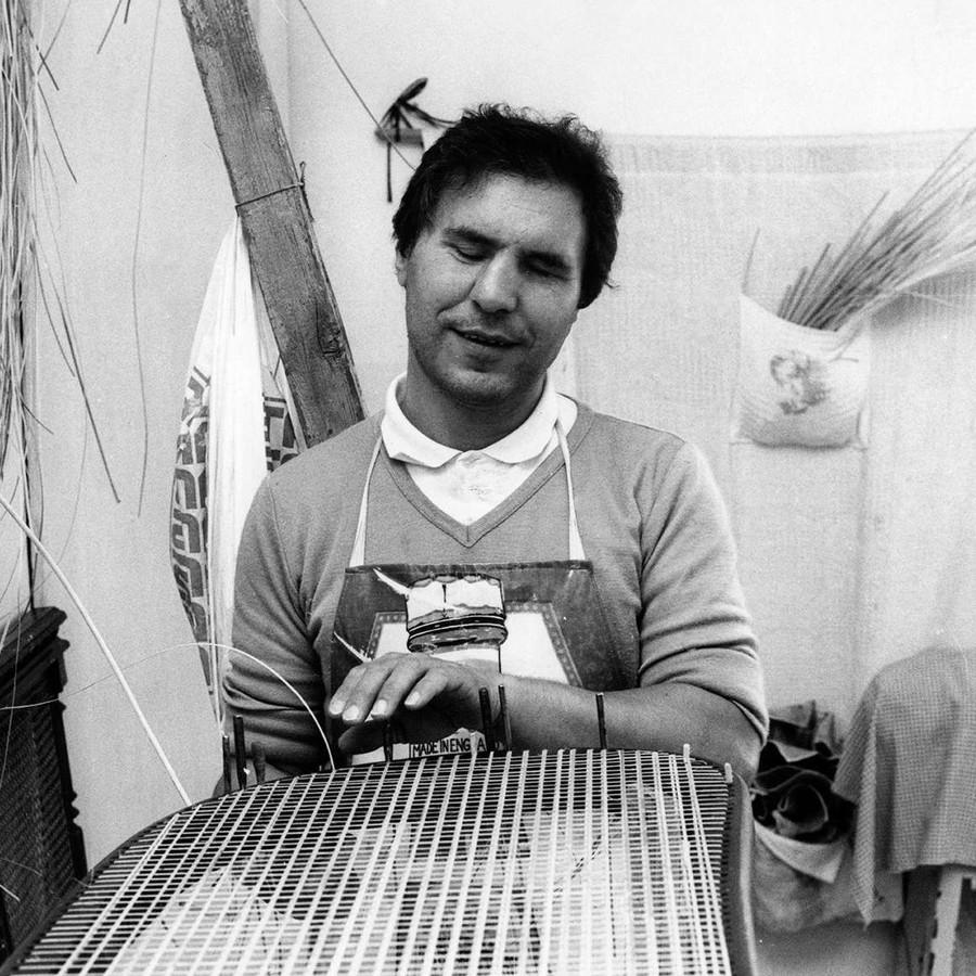 Immagine in bianco e nero degli anni '70. Un uomo sordocieco è fotograto mentre lavora ad un manufatto di vimini.