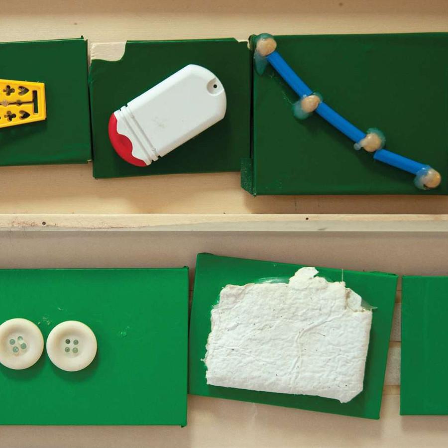 Alcuni tasselli di legno verdi e bianchi sono attaccati a un muro. Su ogni tassello è incollato un oggetto di piccole dimensioni come dei bottoni, oppure dei pezzetti di stoffa o altri materiali, delle cifre come il numero 10 o delle lettere che compongono il nome ALEX.