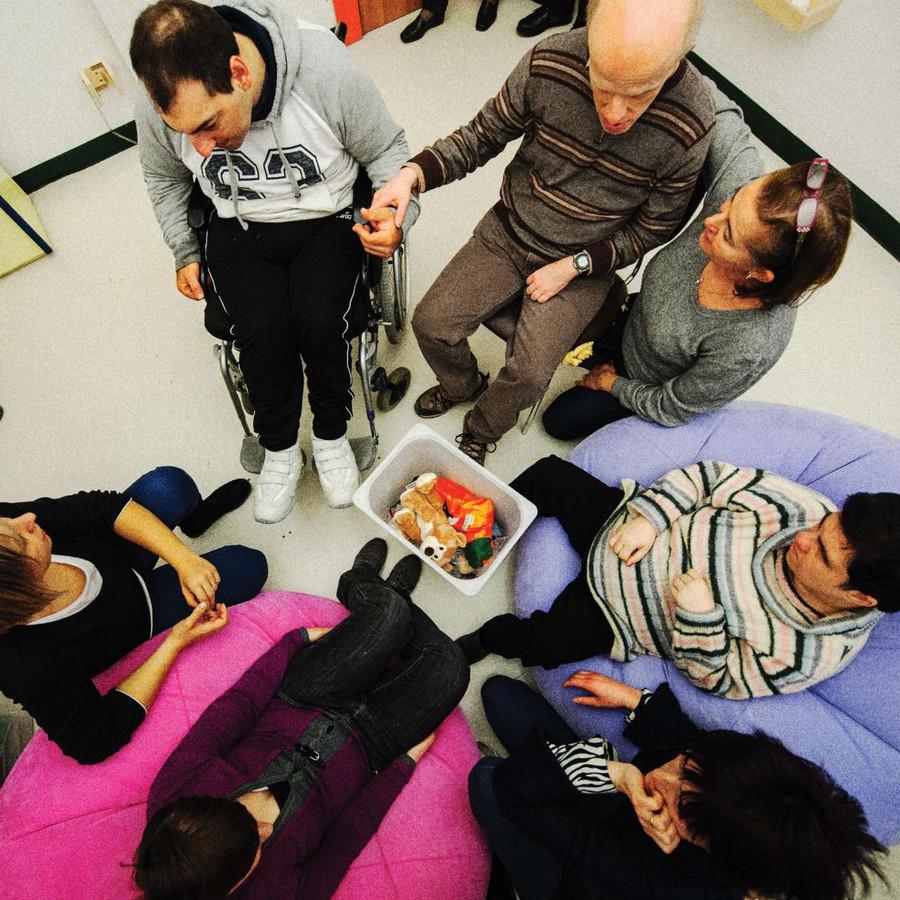 Sette persone, sedute su segie e poltrone, sono fotografate dall'alto. Tra queste ci sono alcuni utenti e dei loro familiari.
