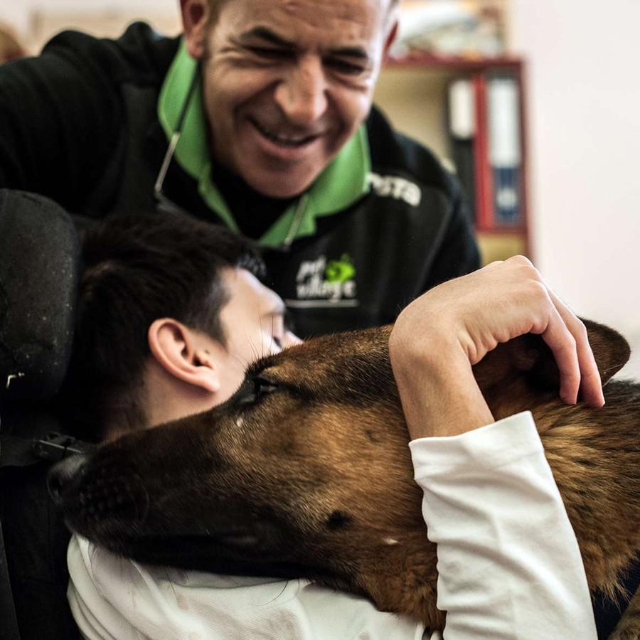 Sotto gli occhi di un operatore sorridente, un ragazzo sordocieco abbraccia un cane pastore tedesco, che appoggia affettuoso la sua testa sulla spalla dell'utente.