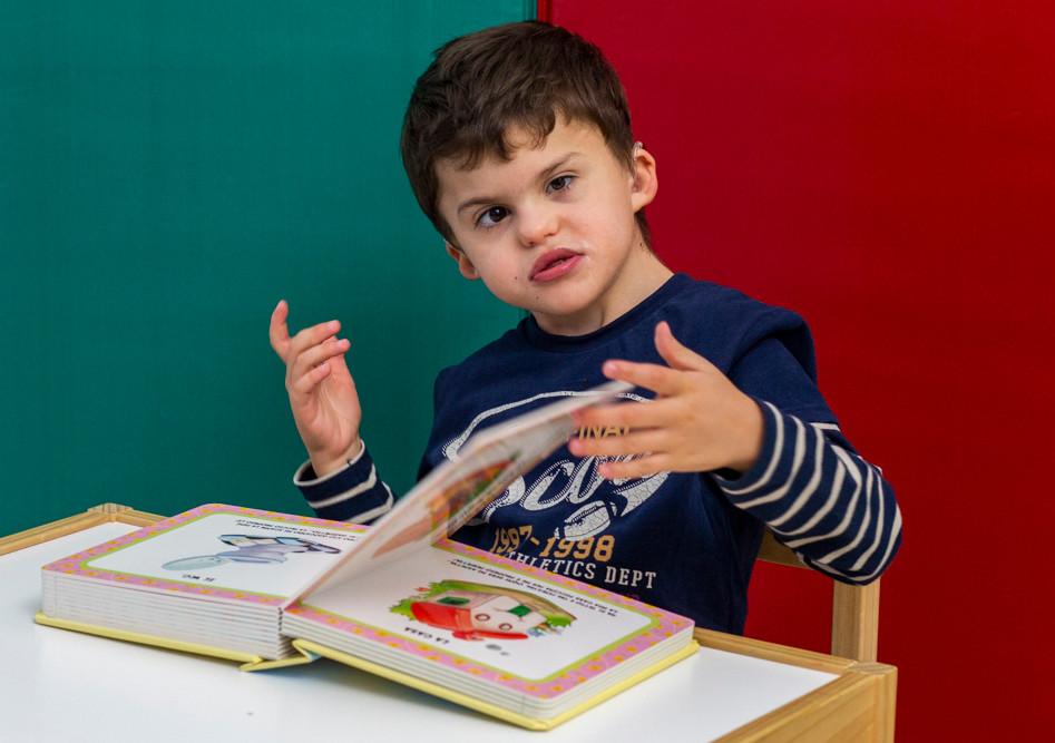 Agostino, un bambino della Lega del Filo d'Oro, sfoglia un libro di favole durante le sue attività riabilitative