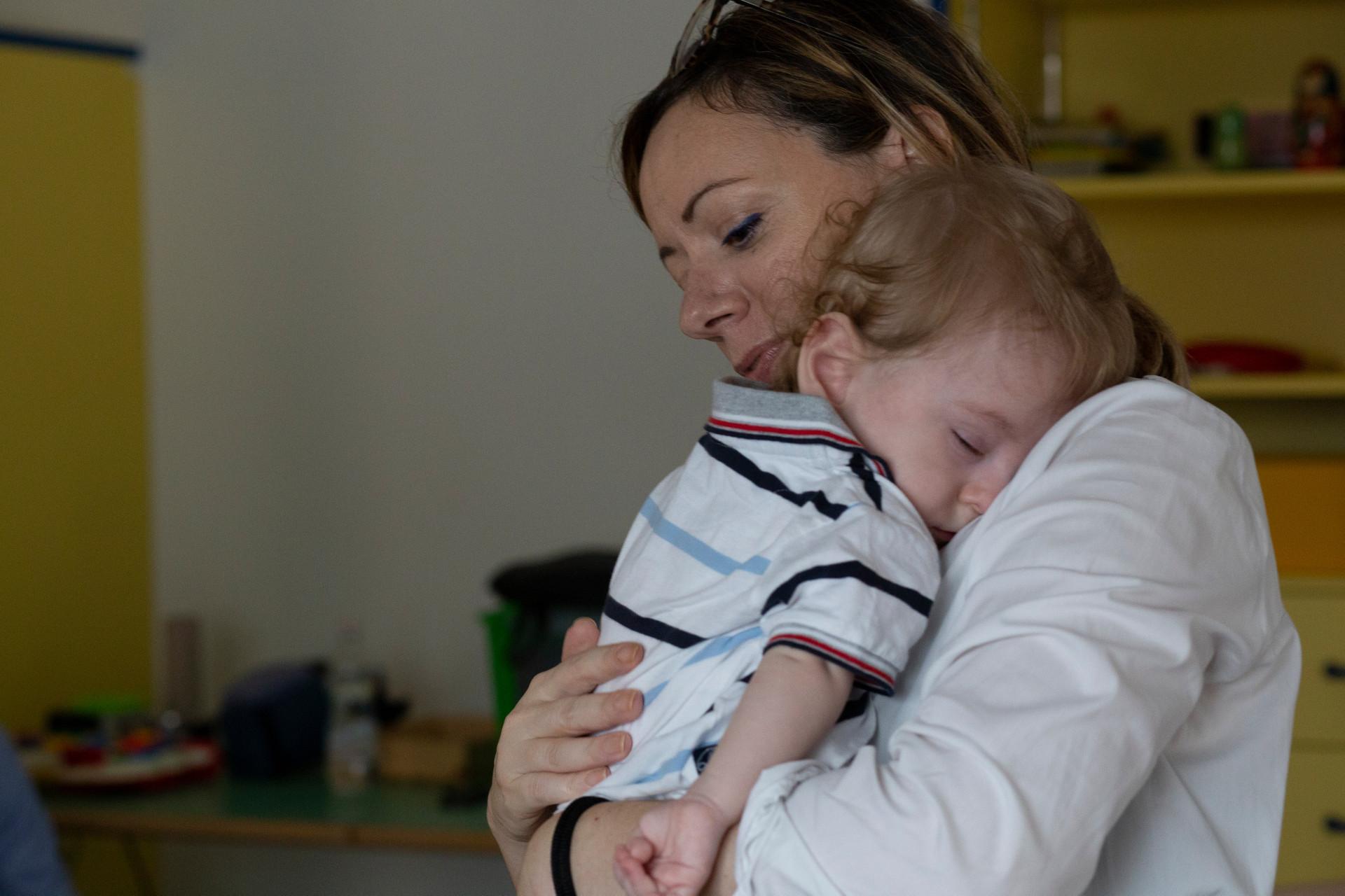 Gabriele dorme tranquillo in braccio a sua mamma, che lo regge accarezzandogli la schiena.
