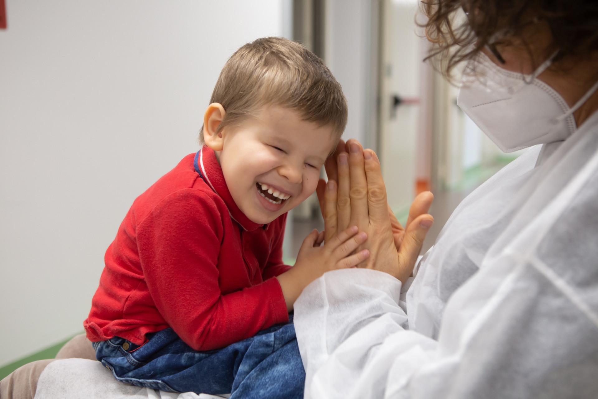 Matteo, piccolo utente del Centro Diagnostico, ride in braccio alla sua educatrice che batte le mani e gioca con lui. L'educatrice indossa camice monouso e mascherina chirurgica