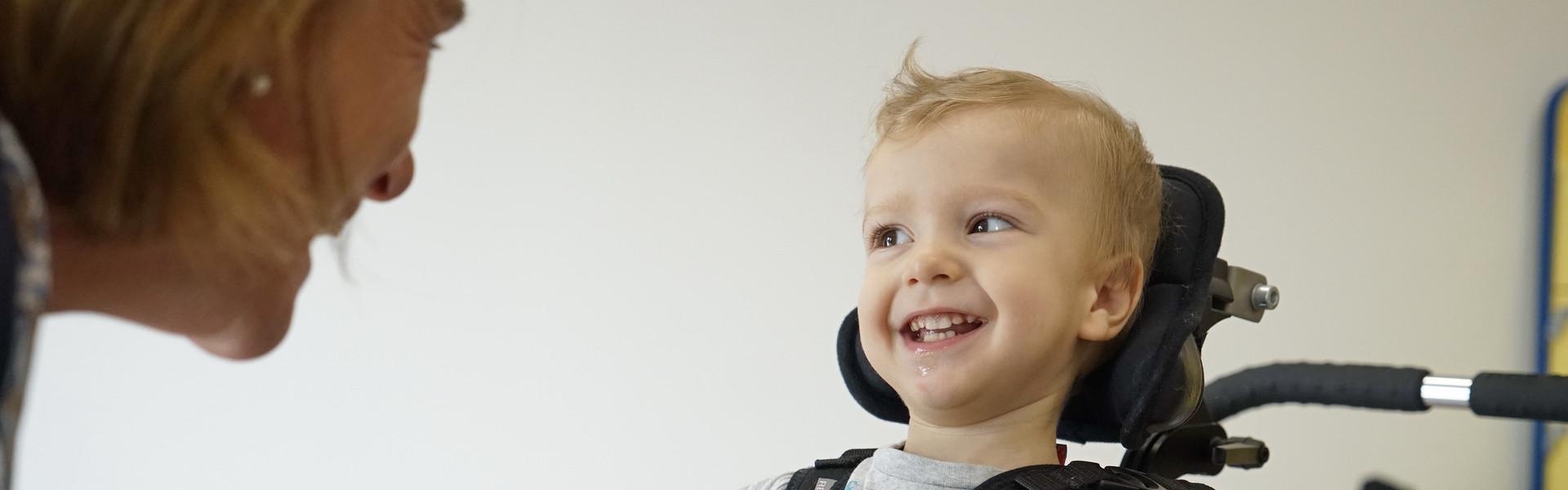Riccardo, piccolo bimbo seguito al Centro di Osimo, è entusiasta dell'attività che sta facendo con la sua educatrice: un grande vassoio di biglie con cui giocare