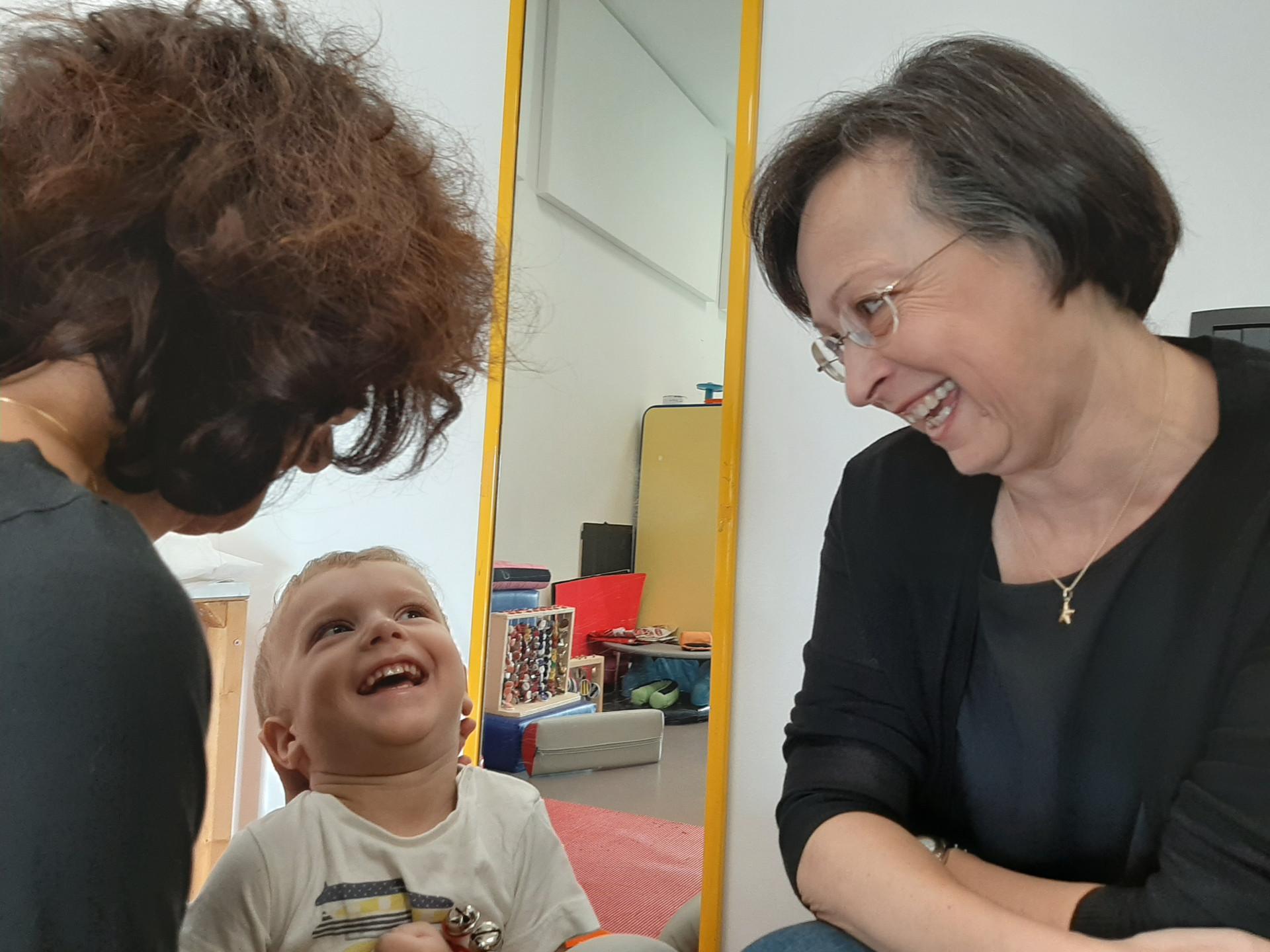 Un bambino utente della Lega del Filo d'Oro ride insieme alla Dottoressa Raimondi, mentre sua mamma, di spalle, lo regge. La scena avviene in un ambiente dedicato alla fisioterapia, come si capisce da alcuni strumenti che si intravedono in uno specchio sullo sfondo.