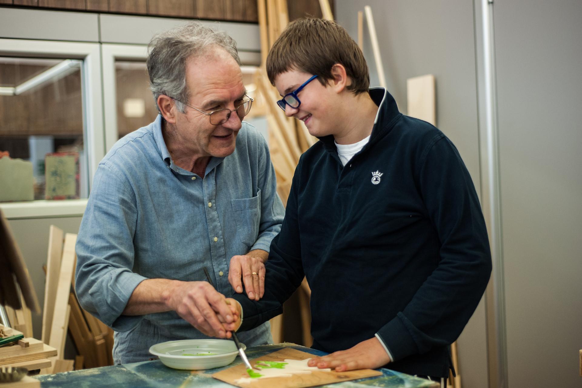 Un volontario chiacchiera con Victor, mentre il ragazzino dipinge col pennello una decorazione natalizia