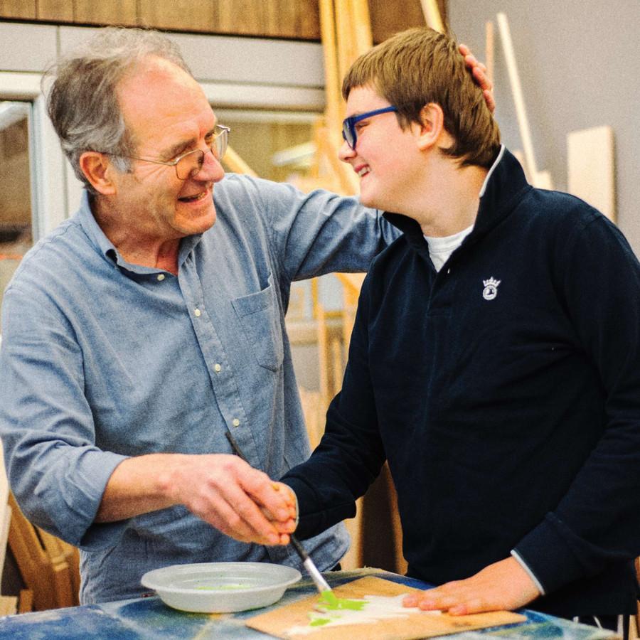 Un utente dipinge con un pennello, aiutato da un uomo che gli accarezza la testa. Entrambi sorridono.