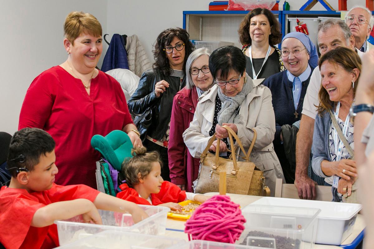 Francesco e Asia svolgono attività riabilitative con una educatrice mentre i sostenitori in visita osservano sorridendo