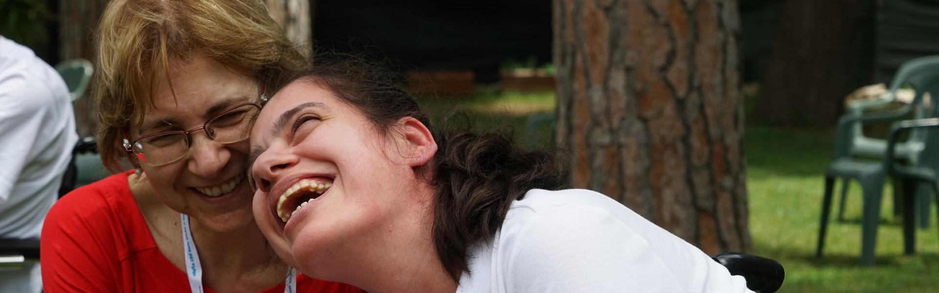 Assemblea delle Famiglie: una volontaria e una giovane utente ridono di gusto insieme guardando o ascoltando qualcosa con uno smartphone