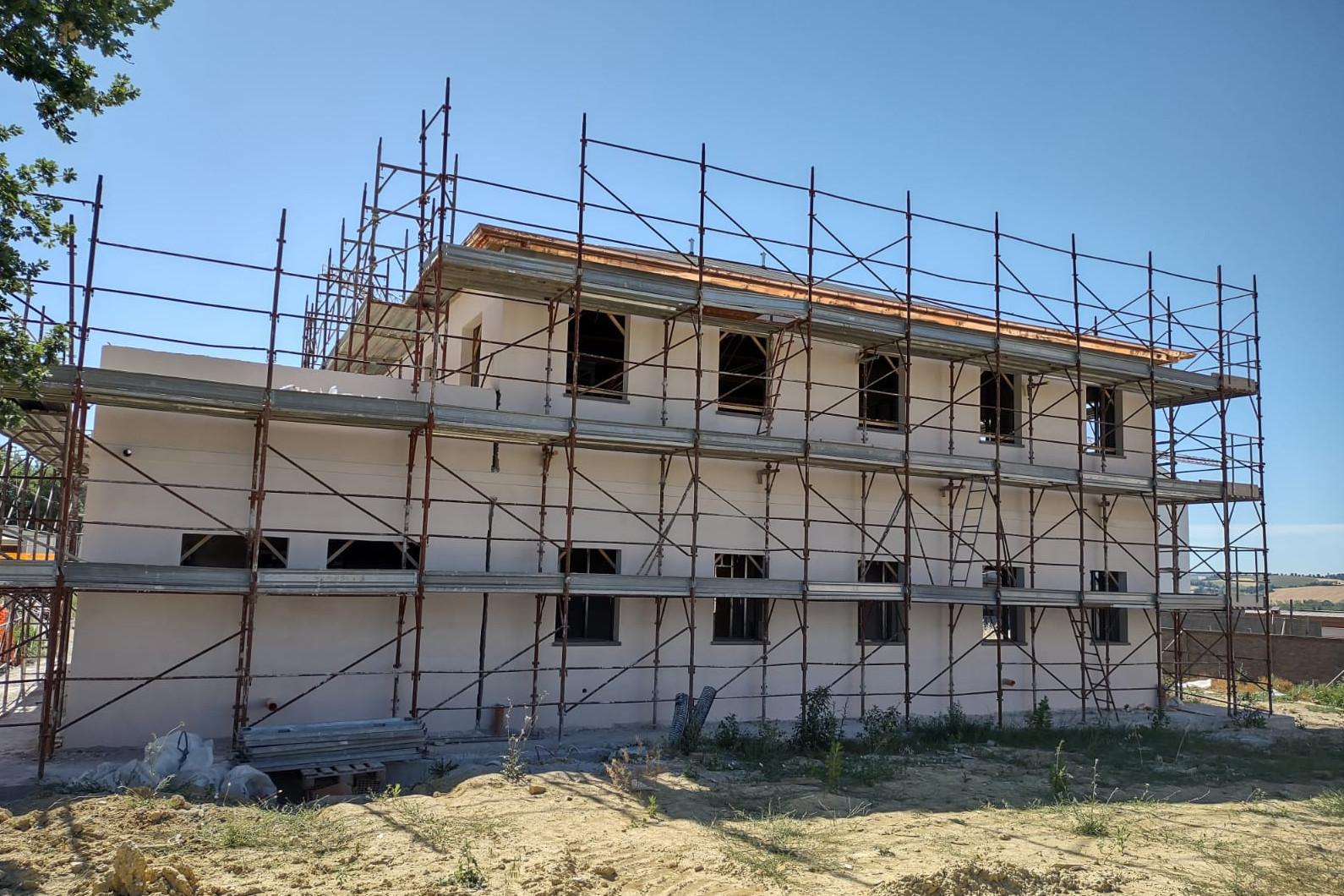La casa colonica in fase di ristrutturazione, con le impalcature e la terra intorno.