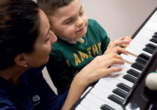 Leonardo bambino utente nel Centro Nazionale di Osimo con Fiammetta, musicoterapista, suona i tasti di un pianoforte
