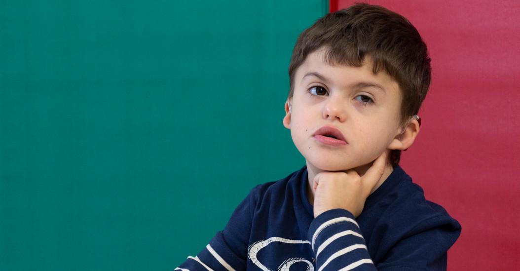 Agostino, bambino di 8 anni con sindrome di Charge, è seduto tranquillo a un banco in attesa di svolgere una attività educativa